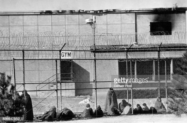 New Mexico Army National Guards men Keep Watch Outside State Penitentiary Inmates behind the fence bundled in blankets are being kept in the prison...