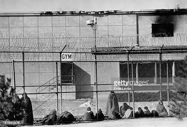 21980 FEB 4 1980 New Mexico Army National Guardsmen keep watch outside state penitentiary Inmates behind the fence bundled in blankets are being kept...