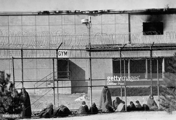New Mexico Army National Guardsmen keep watch outside state penitentiary Inmates behind the fence bundled in blankets are being kept in the prison...