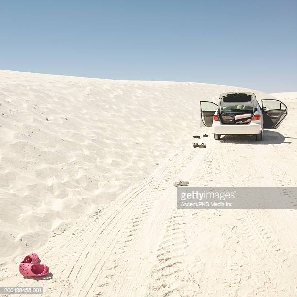 USA, New Mexico, car parked on sand dune, rear view
