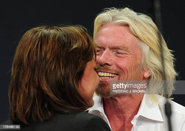 New Mexico Governor Susana Martinez and Sir Richard Branson embrace between speeches inside the hangar facility at Spaceport America, northeast of...