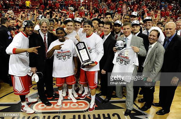 New Mexico Lobos players and coaches celebrate with the trophy after their 6859 win over the San Diego State Aztecs in the championship game of the...