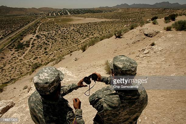 New Mexico National Guard Spec Raymond Rivera and Wyoming National Guard Spec Scott Winters watch the USMexico border from a bluff June 26 2007 near...