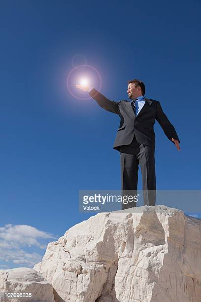 USA, New Mexico, White Sands National Monument, Businessman holding glowing orb on rock