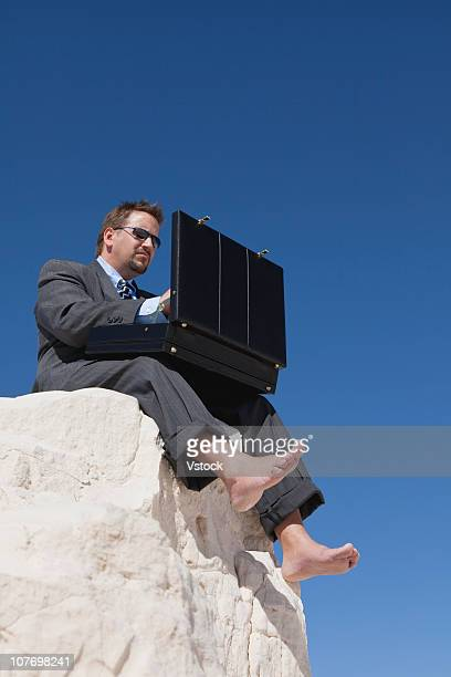 USA, New Mexico, White Sands National Monument, Businessman searching in briefcase on rock