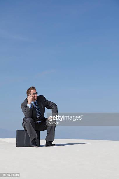 USA, New Mexico, White Sands National Monument, Businessman using mobile phone in desert