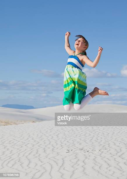 USA, New Mexico, White Sands National Monument, Girl (10-11) jumping in desert