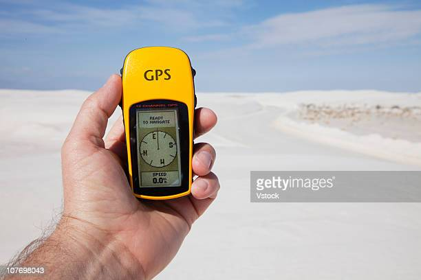 USA, New Mexico, White Sands National Monument, Mans hand holding GPS compass in desert