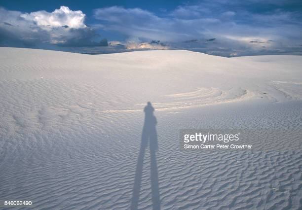 USA, New Mexico, White Sands National Park, shadow of man on sand dune.