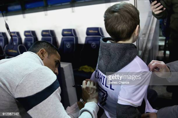 New Millwall signing Tim Cahill signs a shirt for a young fan prior to the Sky Bet Championship match between Millwall and Derby County at The Den on...