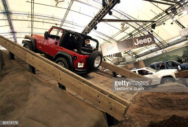 A new model Jeeps power up a ramp built in a indoor pavilion called 'Camp Jeep' during during the 2005 New York Auto Show at the Jacob Javits...