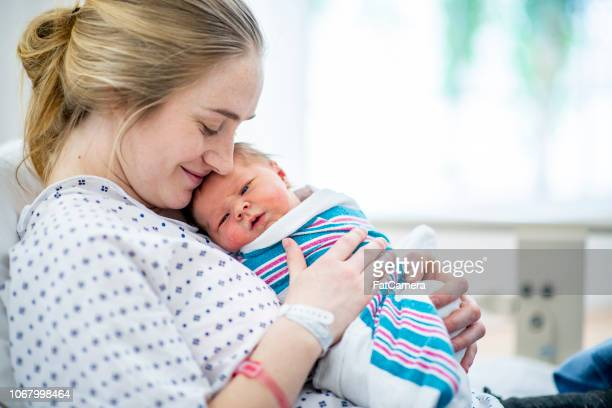 new mom holds her baby in hospital bed - mother foto e immagini stock