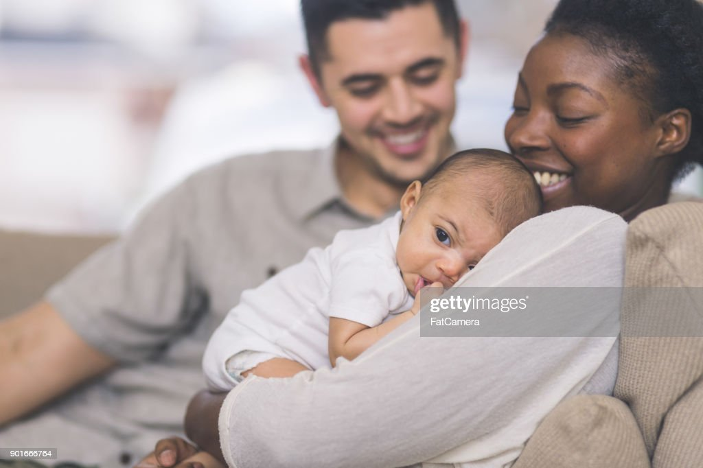 New Mom Holds Her Infant to Her Chest : Stock Photo
