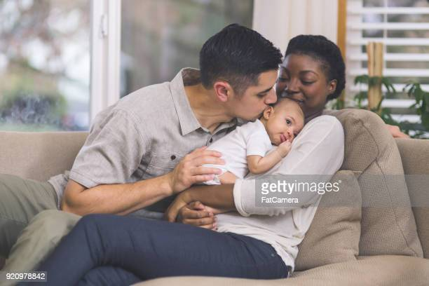 new mom holds her infant to her chest - newborn stock photos and pictures
