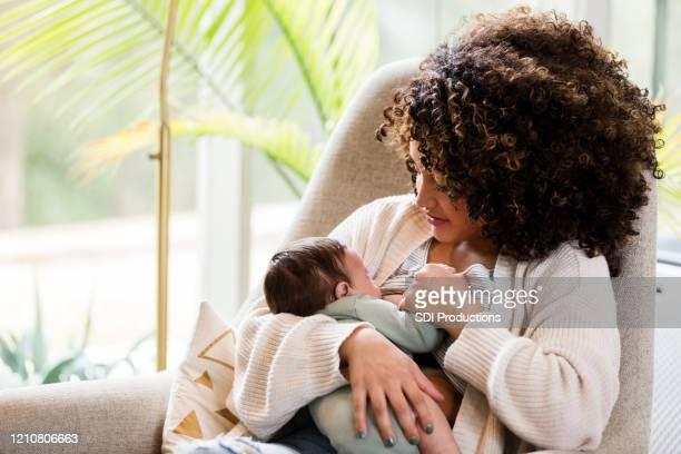 neue mutter stillt baby im wohnzimmer von zu hause - adult breastfeeding stock-fotos und bilder