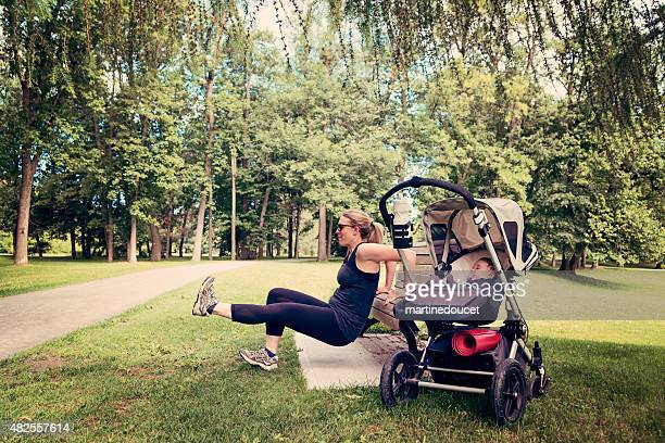 New mother doing exercises with baby sleeping in stroller.