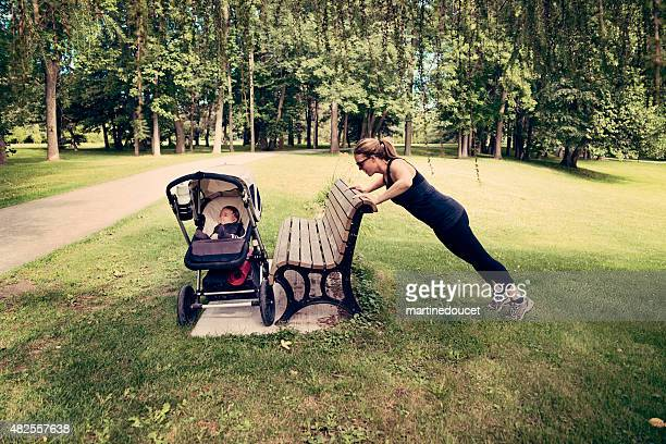 new mother doing exercises with baby sleeping in stroller. - three wheeled pushchair stock pictures, royalty-free photos & images