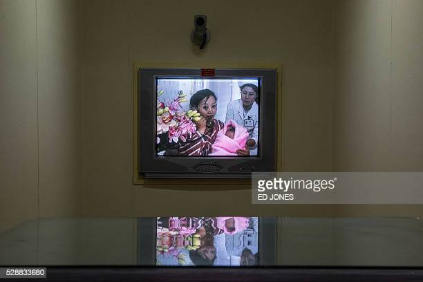 A new mother holds her baby as she talks via telephone on a screen to journalists at the Pyongyang Maternity Hospital during a governmentorganised...