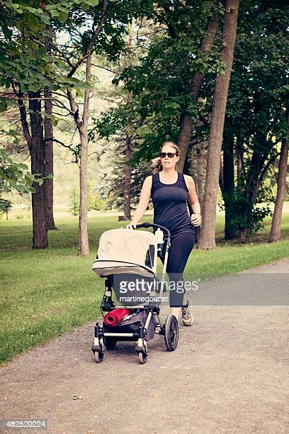 """new mother jogging with stroller in public park. - """"martine doucet"""" or martinedoucet stock pictures, royalty-free photos & images"""