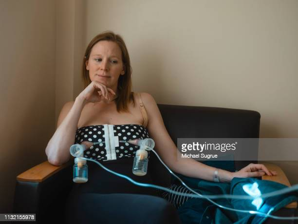 a new mother pumps breast milk in a hospital room. - breast pump stock pictures, royalty-free photos & images