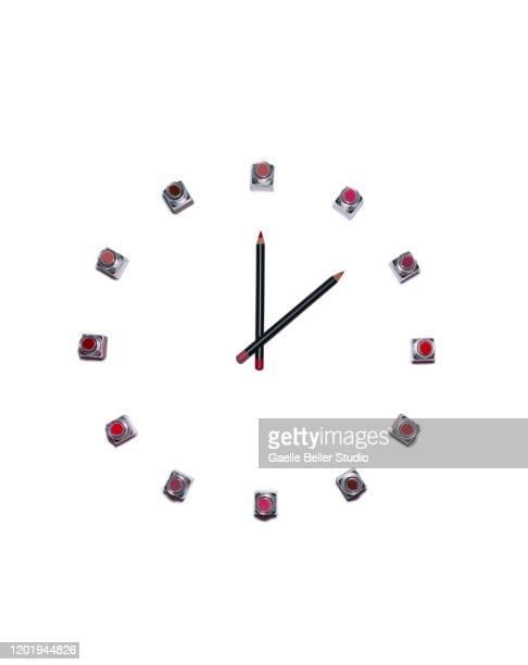 new multi colored lipstick tubes and pencils as clock face - pintalabios rosa fotografías e imágenes de stock