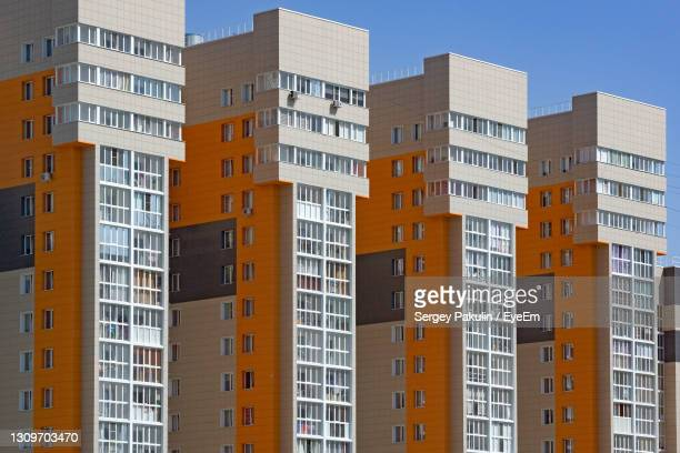 new multi-storey buildings in a row. concept of housing construction for newcomers - mortgage stock pictures, royalty-free photos & images