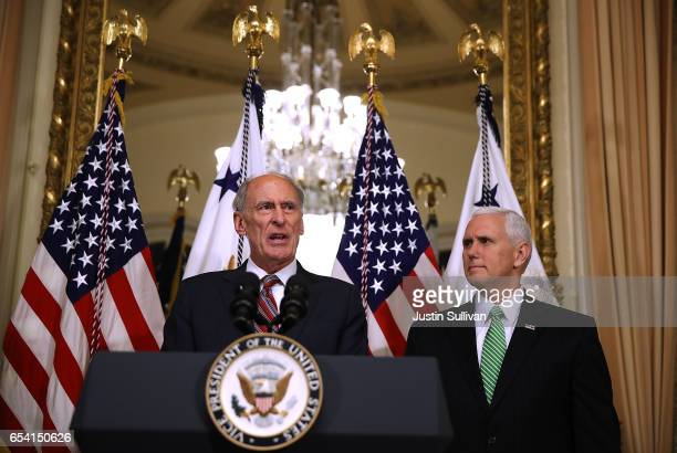 New National Intelligence Director Dan Coats speaks to reporters as US Vice President Mike Pence looks on during Coats' swearingin ceremony at the US...