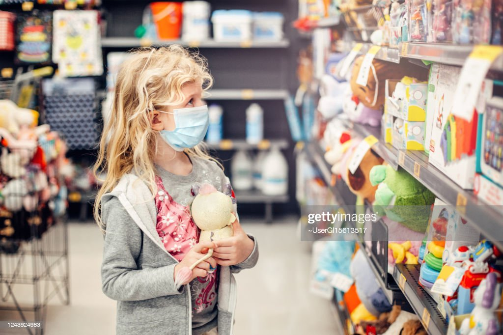 A new normal. Caucasian blonde girl in sanitary face mask shopping at toy store. Child wearing protective mask against coronavirus. Safety, health protection during covid-19 quarantine. : Stock Photo