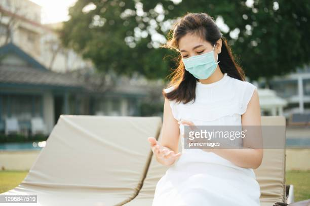 new normal lifestyle asian with protective facemask use hand sanitizer in summer vacation enjoying sunset at beach chair - thai ethnicity stock pictures, royalty-free photos & images