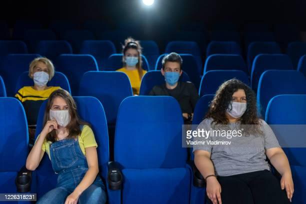 covid-19 neue normalität. publikum im kino. - unterhaltungsveranstaltung stock-fotos und bilder