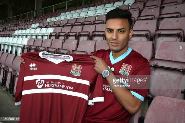 New Northampton Town signing Kashif Saddiqi poses with a shirt during a photo call at Sixfields Stadium on September 10 2013 in Northampton England