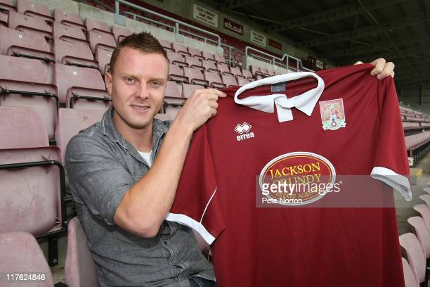 New Northampton Town signing Paul Turnbull poses with a shirt during a photocall on June 29 2011 in Northampton England