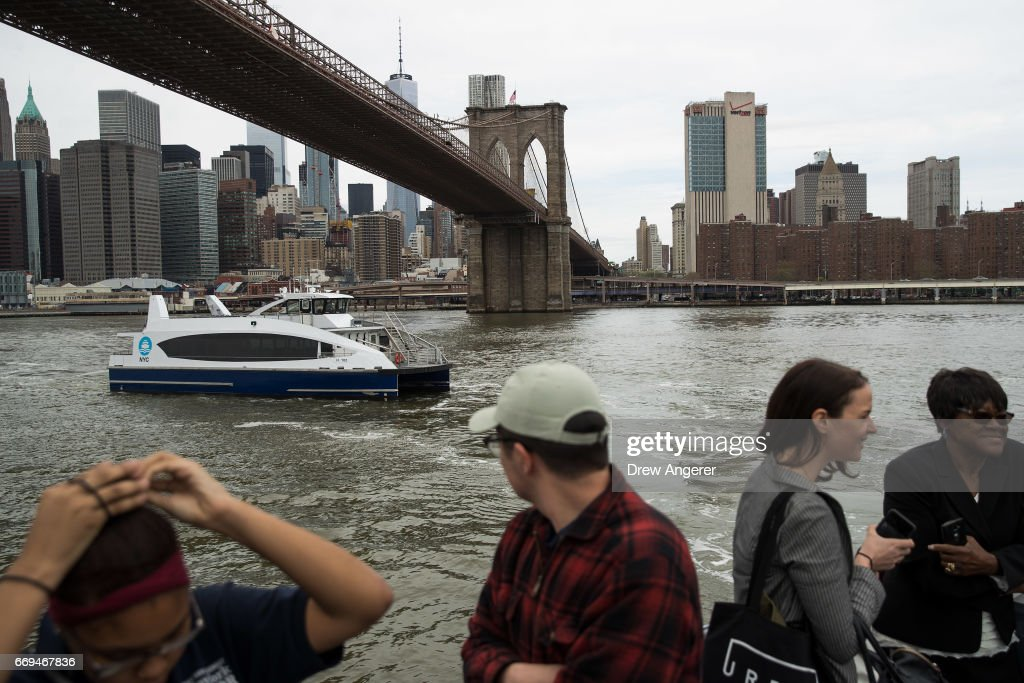 A new NYC Ferry boat passes under the Brooklyn Bridge as