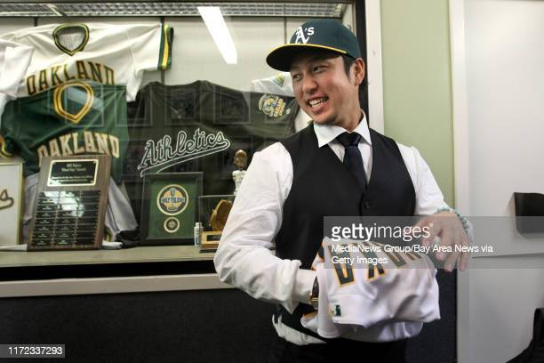 New Oakland Athletics shortstop Hiroyuki Nakajima of Japan folds his new A's jersey after he was photographed in front of retired numbers and other...