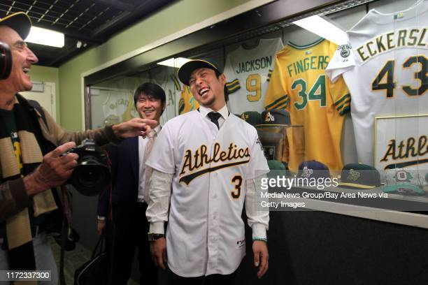 New Oakland Athletics shortstop Hiroyuki Nakajima of Japan is all smiles with A's team photographer Michael Zagaris left as he is photographed in...