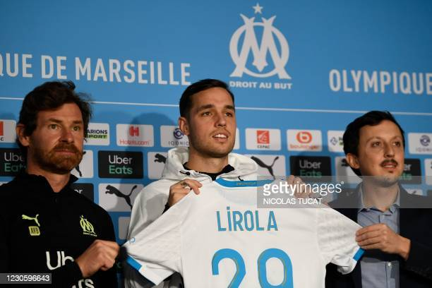 New Olympique de Marseille player Spanish defender Pol Lirola poses with his jersey flanked by Marseille's Portuguese head coach Andre Villas Boas...