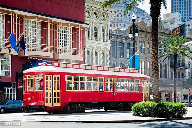 new orleans bright red streetcar traveling amid palms and flags - tram stockfoto's en -beelden
