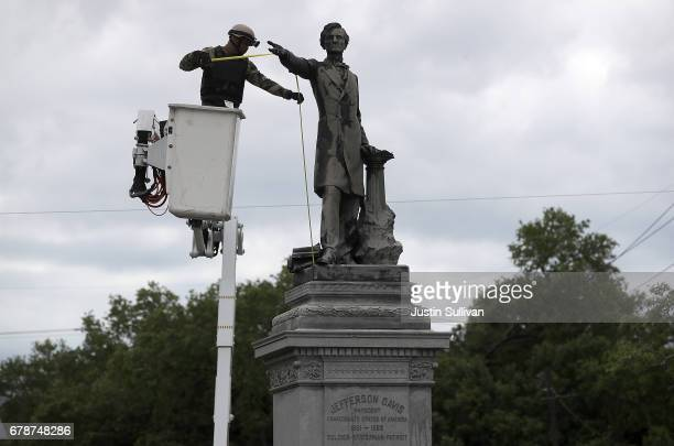 New Orleans city worker wearing body armor and a face covering as he measures the Jefferson Davis monument on May 4 2017 in New Orleans Loiusiana The...