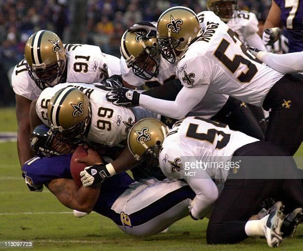 WASHINGTON DC New Orleans' defenders Grady Jackson Norman Hand Sammy Knight Sedrick Hodge and Darrin Smith gang tackle Baltimore running back Jamal...