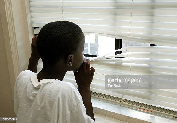 New Orleans evacuee sevenyearold Ayazah Lee looks out a window of a vacant home he hopes soon to be living in during a visit to Chicago Housing...