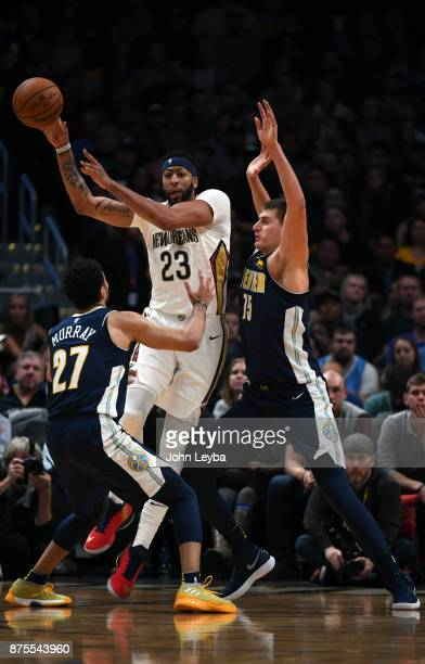 New Orleans Pelicans forward Anthony Davis throws out a pass as he gets double teamed by Denver Nuggets guard Jamal Murray and center Nikola Jokic...