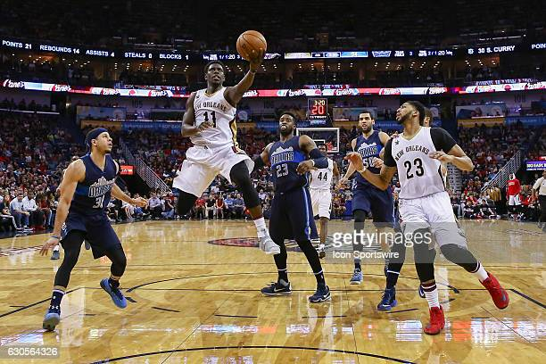 New Orleans Pelicans guard Jrue Holiday drives to the basket against Dallas Mavericks guard Wesley Matthews during the game between the New Orleans...