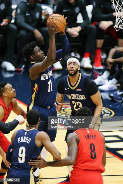 New Orleans Pelicans guard Jrue Holiday drives to the basket against Portland Trail Blazers forward AlFarouq Aminu during the game between the New...