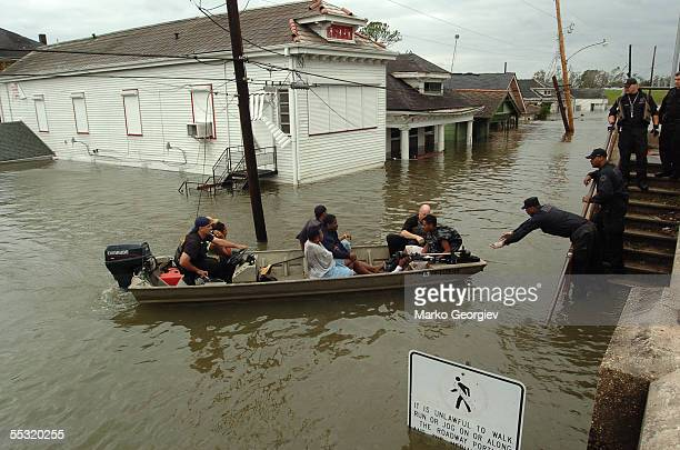New Orleans police bring people ashore from the rescue boats at the flooded Lower Ninth Ward in New Orleans, Louisiana on August 29, 2005. Hurricane...