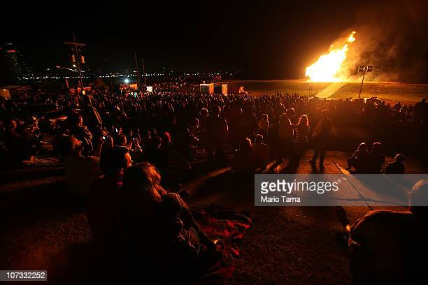 New Orleans residents look on as the traditional Algiers Point Christmas bonfire burns on the Mississippi River levee December 4, 2010 in New...
