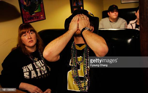 New Orleans Saints fans Jeff Brooks right holds his face after Colts scored 1st touchdown of Super Bowl by his wife Karen at Bayou Bob's in downtown...