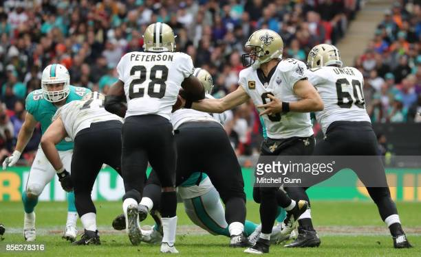 New Orleans Saints quarterback Drew Brees hands off to New Orleans Saints running back Adrian Peterson during the NFL match between the Miami...