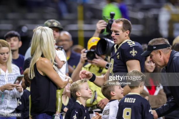 New Orleans Saints quarterback Drew Brees takes a moment to spend with his wife and children that are playing with head coach Sean Payton in an NFL...