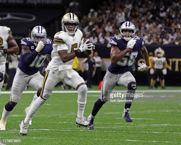 New Orleans Saints quarterback Teddy Bridgewater scrambles out the pocket being chased by Dallas Cowboys defensive end Robert Quinn and defensive end...