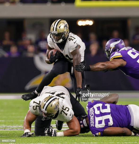 New Orleans Saints running back Alvin Kamara has to leap over offensive guard Andrus Peat to avoid the tackle of Minnesota Vikings defensive tackle...